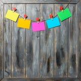Farbiges Papier bedeckt auf Thread mit Herz geformtem hölzernem Hintergrund der Wäscheklammer Stockbilder
