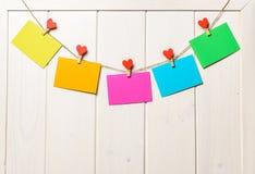 Farbiges Papier bedeckt auf Thread mit Herz geformtem weißem hölzernem Hintergrund der Wäscheklammer Lizenzfreies Stockfoto