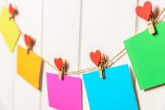 Farbiges Papier bedeckt auf Thread mit Herz geformtem weißem hölzernem Hintergrund der Wäscheklammer Stockfotografie