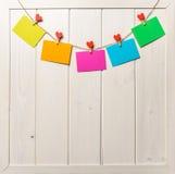 Farbiges Papier bedeckt auf Thread mit Herz geformtem weißem hölzernem Hintergrund der Wäscheklammer Stockfoto