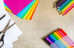 Farbiges Papier, Filzstifte, Bleistifte und Scheren auf hölzernem Hintergrund Stockbild