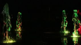 Farbiges Wassernachtbrunnentanzen mit Unschärfe-Gesamtlängenhintergrund der Lichter mehrfarbigem, Abschluss oben, flache Tiefe de stock video footage