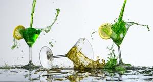 Farbiges Wasserspritzen im Glas und in der Zitrone stockbilder