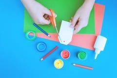 Farbpapier, -farbe und -hände mit Scheren stockfotografie