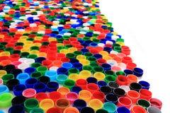 Farbplastik bedeckt Hintergrund mit einer Kappe Lizenzfreie Stockfotografie