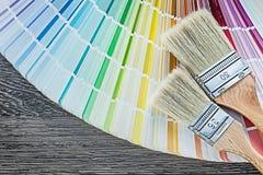 Farbprobenehmerpinsel auf hölzernem Brett Stockbilder