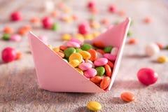 Farbsüßigkeit auf Papierboot Stockbild