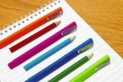 Farbstifte und Bleistifte auf einem Notizblock Lizenzfreie Stockbilder