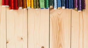 Farbthreads auf einem Holztisch Lizenzfreies Stockbild