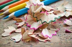 Farbtonbleistifte und Bleistiftschnitzel auf hölzernem Schreibtisch Lizenzfreie Stockbilder