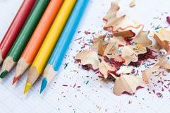 Farbtonbleistifte und Bleistiftschnitzel auf Notizbuch Lizenzfreie Stockfotografie