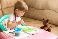 Farbtonzeichnungen des kleinen Mädchens, die am Tisch, Entwicklung des Kindes sitzen Stockbilder