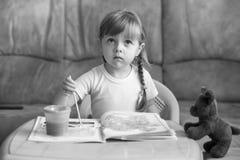 Farbtonzeichnungen des kleinen Mädchens, die am Tisch, Entwicklung des Kindes sitzen Stockbild