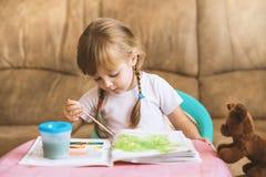 Farbtonzeichnungen des kleinen Mädchens, die am Tisch, Entwicklung des Kindes sitzen Stockfotografie
