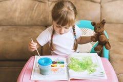Farbtonzeichnungen des kleinen Mädchens, die am Tisch, Entwicklung des Kindes sitzen Lizenzfreie Stockfotos