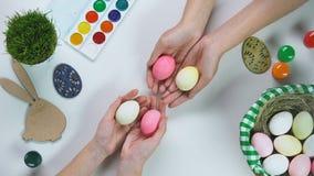 Farbujący jajka w żeńskich rękach, Wielkanocnego królika dekoracji i wakacje koszu na stole, zbiory
