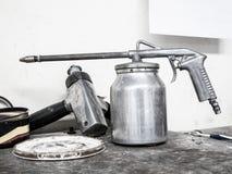Farby kiści pistolet na drewno stole w samochodowym remontowym usługowym centrum Fotografia Stock