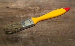 Farby muśnięcia szerokość 1 cal z żółtą rękojeścią na drewnianym tle obraz royalty free