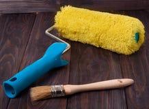 Farby muśnięcie na drewnianym tle i rolownik fotografia stock
