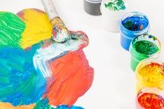 Farby Różni kolory i farby muśnięcie na bielu stole Obraz Stock