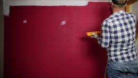 farby rolownika próbki Mężczyzna w czerwonym kapeluszu barwi pokój z farba rolownikiem farby muśnięciem i zbiory