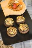 Farci champignons on black plate Stock Photography