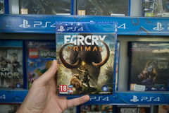 Farcry Primal. Bratislava, Slovakia, circa april 2017: Man holding Farcry Primal videogame on Sony Playstation 4 console in store Royalty Free Stock Images