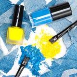 Fard à paupières bleu et jaune avec des vernis à ongles des mêmes couleurs Images stock