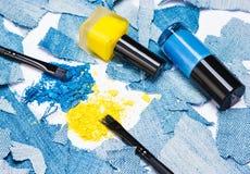 Fard à paupières bleu et jaune avec des vernis à ongles des mêmes couleurs Photo stock
