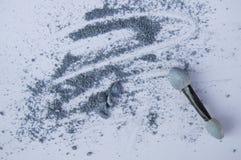 Fard à paupières bleu ou gris avec l'applicateur sur le fond blanc photographie stock