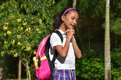 Farda da escola asiática bonito de In Prayer Wearing do estudante fêmea com livros foto de stock