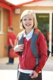 Farda da escola vestindo da menina que está no campo de jogos Foto de Stock Royalty Free