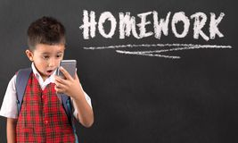Farda da escola vestindo do menino que olha o telefone celular com express?o chocada em sua cara foto de stock royalty free
