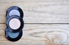 Fards à paupières dans des boîtes noires et brosse sur la table en bois Photo stock