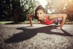 Fare adatto della giovane donna spinge verso l'alto l'esercizio nel parco al sunse Motivazione di sport Concetto di salute Fotografia Stock Libera da Diritti