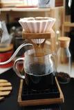 Fare caffè in dispositivo di gocciolamento ceramico rosa di origami con l'esclusione Supporto di legno Miscela manuale alternativ fotografia stock libera da diritti