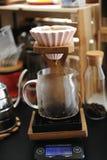 Fare caffè in dispositivo di gocciolamento ceramico rosa di origami sul supporto di legno Miscela manuale alternativa Scala elett fotografia stock
