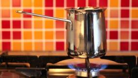 Fare caffè nel cezve del inox su una stufa di gas stock footage