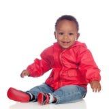 Fare da baby-sitter africano adorabile sul pavimento con l'impermeabile rosso Fotografia Stock Libera da Diritti