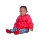 Fare da baby-sitter africano adorabile sul pavimento con l'impermeabile rosso Fotografia Stock