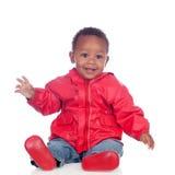 Fare da baby-sitter africano adorabile sul pavimento con l'impermeabile rosso Immagini Stock
