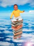 Fare da baby-sitter africano sulla pila di libri Immagine Stock