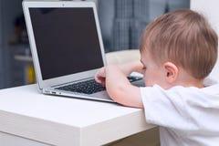 Fare da baby-sitter al computer portatile ed al gioco Immagine Stock