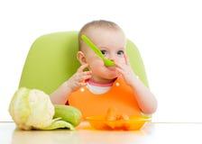 Fare da baby-sitter alla tavola con alimento sano Fotografia Stock