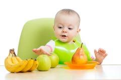 Fare da baby-sitter alla tavola con i frutti Fotografia Stock