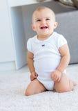 Fare da baby-sitter allegro sveglio su tappeto Fotografia Stock Libera da Diritti