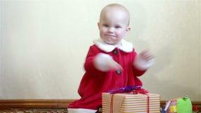 Fare da baby-sitter, applaudente, derzhitkorobku con un regalo stock footage