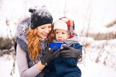 Fare da baby-sitter con il te caldo bevente esterno della giovane bella madre Fotografia Stock Libera da Diritti