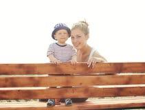 Fare da baby-sitter del figlio e della madre insieme sul banco Fotografia Stock