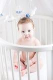 Fare da baby-sitter molto bello in una greppia rotonda bianca Fotografia Stock Libera da Diritti